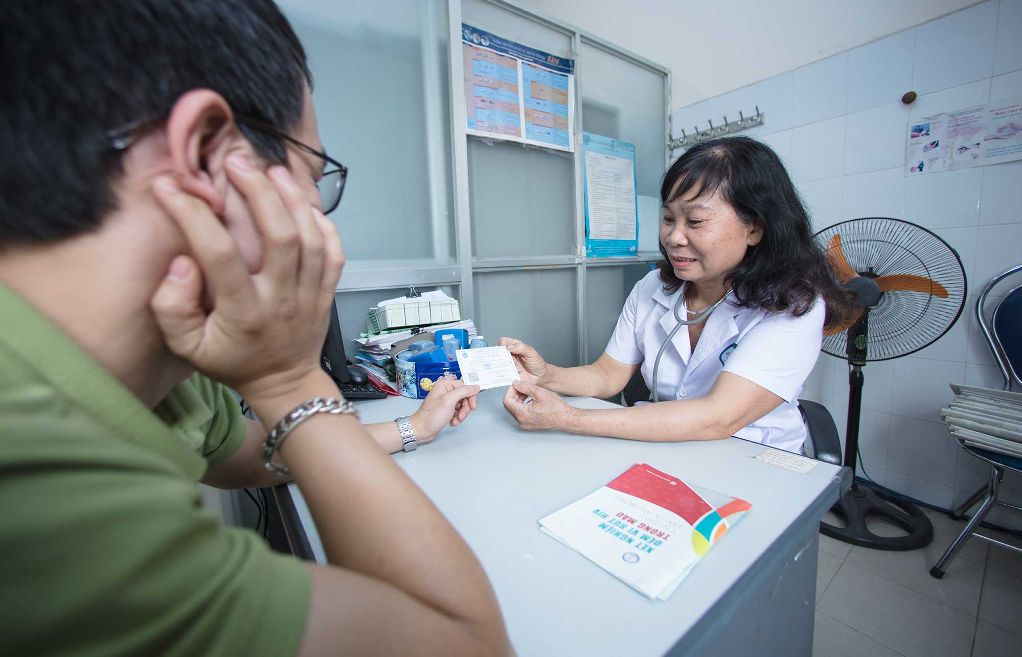 Health care worker in Vietnam speaking to patient